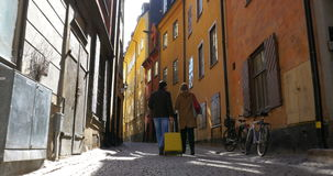 Touristic walk in Old Town of Stockholm. Steadicam back shot of a male and female tourists walking along the narrow cobbled street and looking at ancient houses stock video