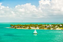Touristic yacht floating by green island at Key West, Florida. Cruise touristic boat or yacht floating by island with houses and green trees on turquoise water royalty free stock photography