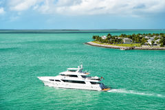 Touristic yacht floating near green island at Key West, Florida. Cruise touristic boat or yacht floating near island with houses and green trees on turquoise Stock Photography