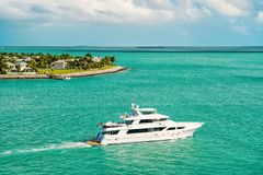 Touristic yacht floating near green island at Key West, Florida. Cruise touristic boat or yacht floating near island with houses and green trees on turquoise royalty free stock image