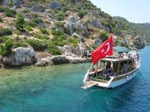 Touristic yacht with turkish flag near Kekova Island. Ruins of sunken city Kekova and touristic yacht with turkish national flag. Photo taken in Antalya region Royalty Free Stock Images