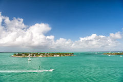 Touristic yachts floating by green island at Key West, Florida. Cruise touristic boats or yachts floating by island with houses and green trees on turquoise stock photography