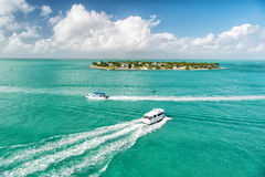 Touristic yachts floating by green island at Key West, Florida. Cruise touristic boats or yachts floating by island with houses and green trees on turquoise royalty free stock photos