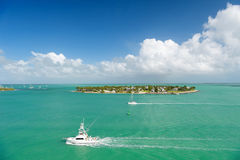 Touristic yachts floating by green island at Key West, Florida. Cruise touristic boats or yachts floating by island with houses and green trees on turquoise stock image