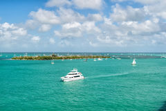 Touristic yachts floating by green island at Key West, Florida. Cruise touristic boats or yachts floating by island with houses and green trees on turquoise stock photo