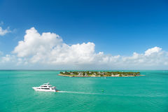 Touristic yachts floating by green island at Key West, Florida. Cruise touristic boats or yachts floating by island with houses and green trees on turquoise Royalty Free Stock Images