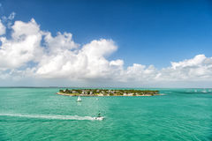 Touristic yachts floating by green island at Key West, Florida. Cruise touristic boats or yacht floating by island with houses and green trees on turquoise water stock photos