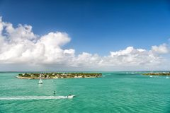 Touristic yachts floating by green island at Key West, Florida. Cruise touristic boats or yacht floating by island with houses and green trees on turquoise water royalty free stock images
