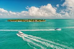 Touristic yachts floating by green island at Key West, Florida. Cruise touristic boats or yacht floating by island with houses and green trees on turquoise water royalty free stock photo