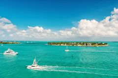 Touristic yachts floating by green island at Key West, Florida. Cruise touristic boats or yachts floating by island with houses and green trees on turquoise stock images