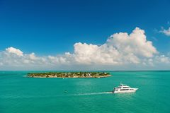 Touristic yachts floating by green island at Key West, Florida. Cruise touristic boats or yachts floating by island with houses and green trees on turquoise royalty free stock image