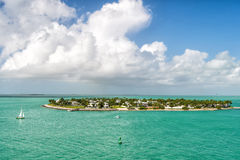 Touristic yachts floating near green island at Key West, Florida. Cruise touristic boats or yachts floating near island with houses and green trees on turquoise Stock Photography