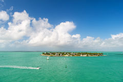 Touristic yachts floating near green island at Key West, Florida. Cruise touristic boats or yachts floating near island with houses and green trees on turquoise Royalty Free Stock Photo