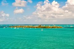 Touristic yachts floating near green island at Key West, Florida. Cruise touristic boats or yachts floating near island with houses and green trees on turquoise stock photo