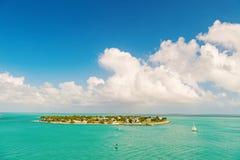 Touristic yachts floating near green island at Key West, Florida. Cruise touristic boats or yachts floating near island with houses and green trees on turquoise stock image