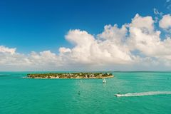 Touristic yachts floating near green island at Key West, Florida. Cruise touristic boats or yachts floating near island with houses and green trees on turquoise royalty free stock image