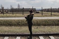 Touristisch, ein Foto auf der Eisenbahn machend, die zu Haupteingang von Konzentrationslager Auschwitz Birkenau, Polen am 12. Mär lizenzfreie stockbilder
