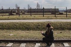 Touristisch, ein Foto auf der Eisenbahn machend, die zu Haupteingang von Konzentrationslager Auschwitz Birkenau, Polen am 12. Mär stockfotos