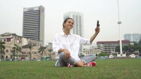 Touristisch nehmen Sie Fotos und selfies auf Gras in Kuala Lumpur lizenzfreies stockbild
