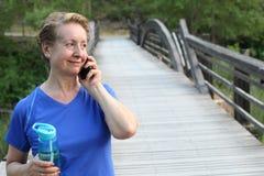 Touristische ältere Frau, die Zellintelligente Telefonanruf-Lächeln-Sommerferien-Grünbaumpark-Reisekommunikation verwendet lizenzfreies stockfoto