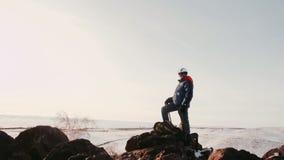 Touristische Ausrüstung des Mannes ist an der Spitze des Berges und der Blicke in den Abstand das Betreibertriebvideo es durch stock footage