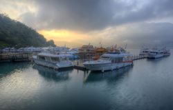 Touristische Boote festgemacht zu den Docks während der teilweisen Sonnenfinsternis an Shuishe-Pier von Sonne-Mond-See in Nantou Stockfotografie