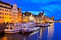 Touristische Boote und bunte historische Häuser nachts Stockbilder