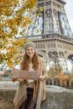 Touristische Frau auf Damm nahe Eiffelturm in Paris mit Karte Stockfotografie