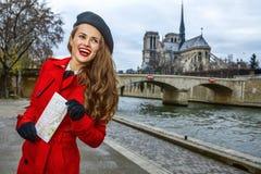 Touristische Frau auf Damm nahe Notre Dame de Paris mit Karte Stockbilder