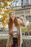 Touristische Frau auf Damm in Paris, das Karte und das Zeigen hält Lizenzfreies Stockfoto