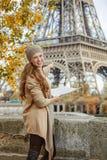 Touristische Frau auf Damm in Paris, das Karte und das Zeigen hält Stockfotografie