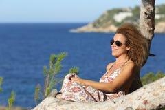 Touristische Frau, die auf dem Strand in Ferien sich entspannt Stockbild