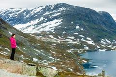 Touristische Frau, die Djupvatnet See, Norwegen bereitsteht Lizenzfreie Stockfotografie