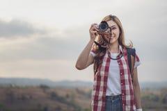 Touristische Frau, die Foto mit ihrer Kamera in der Natur macht stockfotos