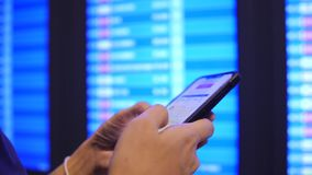 Touristische Frau, die ihre Flugzeit unter Verwendung des Handys nahe Abfahrt-Brett im Flughafen überprüft 4K Slowmotion Bangkok, stock footage