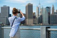 Touristische Frau, die Reisephoto mit Kamera von Manhattan-Skyline- und New- York Cityskylinen während der Herbstferien macht lizenzfreie stockfotografie