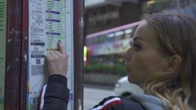 Touristische Frau, die Zeitplan und Wegpassagierbusse in der Station in modernasian Stadt m schaut Reisendfrauenaufpassen stock footage