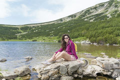 Touristische Frau im Berg auf einem bezbog Seehintergrund lizenzfreie stockfotografie