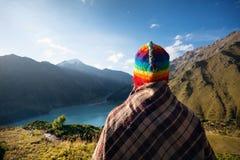 Touristische Frau im Regenbogenhut an den Bergen lizenzfreie stockbilder