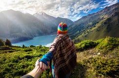 Touristische Frau im Regenbogenhut an den Bergen lizenzfreies stockbild