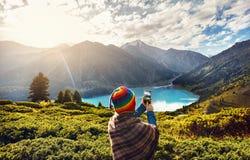 Touristische Frau im Regenbogenhut an den Bergen lizenzfreie stockfotografie