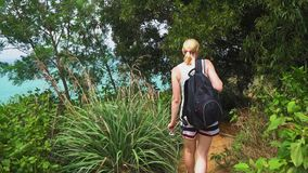 Touristische Frau mit einem Rucksack gehend auf einen tropischen Wald auf der Insel stock footage