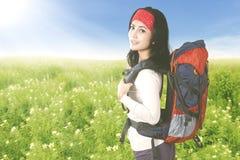 Touristische Frau mit Rucksack auf dem Blumengebiet Stockbilder