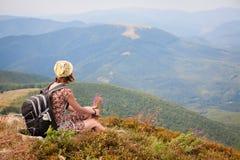 touristische Frau mit Rucksack im Sommerkleid mit Blumen Ansicht genießend Trekking in den Bergen lizenzfreie stockbilder