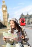 Touristische Frauenbesichtigung Londons, die Karte hält Lizenzfreie Stockfotos