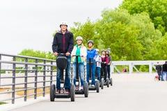 Touristische Gruppe, die Segway am Sightseeing-Tour fährt Lizenzfreies Stockbild