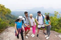 Touristische Gruppen-Uhr-Fotos an den Zellintelligenten Telefonen, Leute mit Rucksack über Landschaft von der Gebirgsspitze lizenzfreie stockfotografie