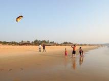 Touristische Herstellungsfliege ein Drachen auf dem Strand von Candolim Lizenzfreie Stockfotografie