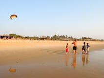Touristische Herstellungsfliege ein Drachen auf dem Strand von Candolim Lizenzfreie Stockbilder