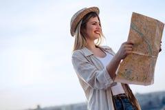Touristische junge Frau, die Karte betrachtet und Stadt erforscht lizenzfreie stockbilder